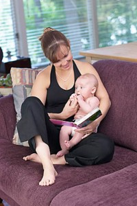 Woman reading book and holding baby in living room